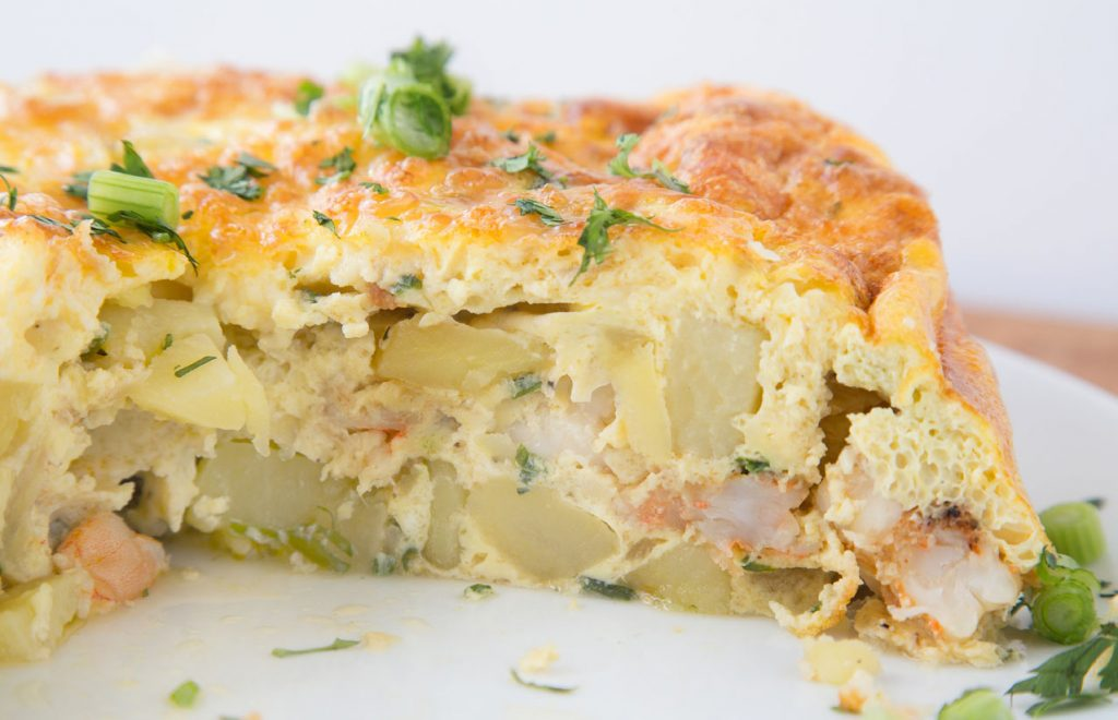 Cut view of Spanish Shrimp tortilla on white plate garnished with scallions and parsley
