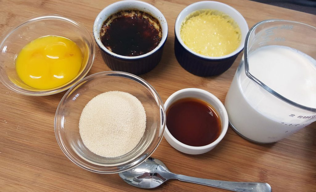 ingredients to make creme brulee on a wooden cutting board
