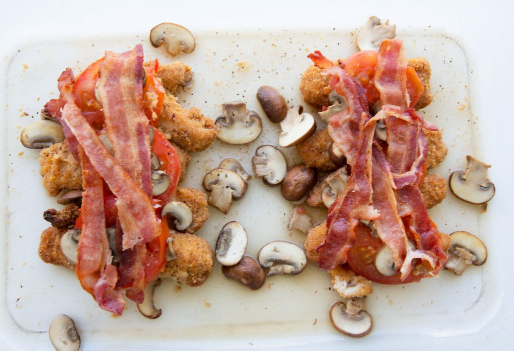 chicken strips topped with tomatoes and bacon in a baking dish with cooked sliced mushrooms
