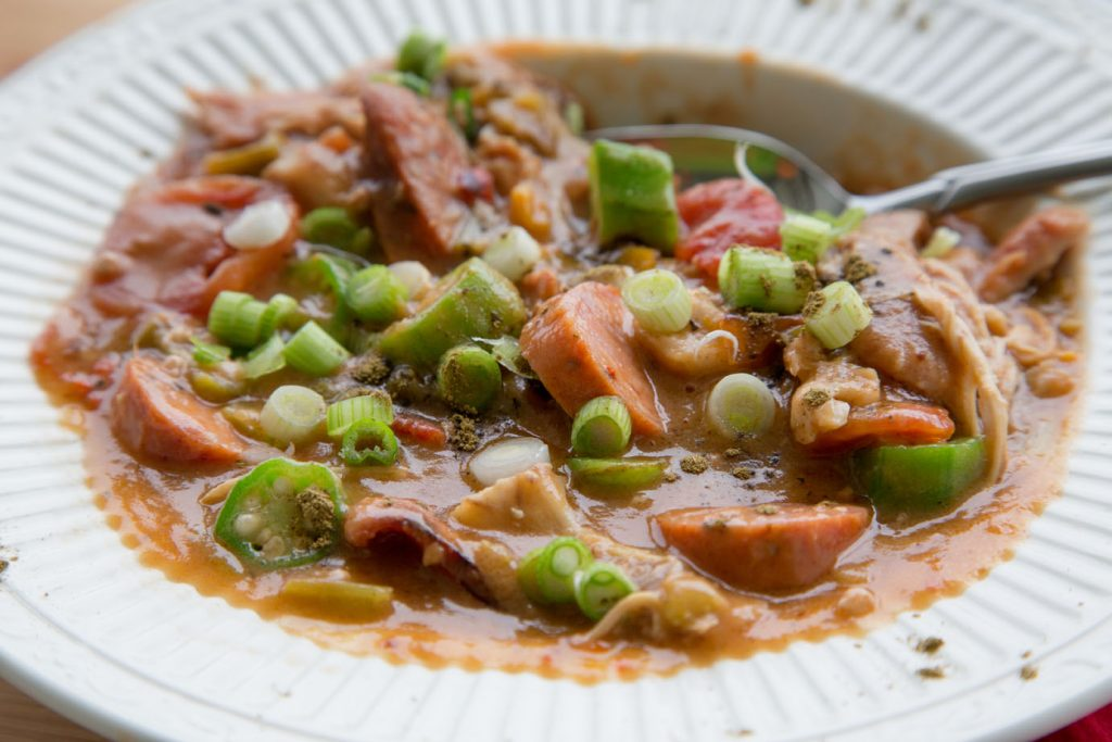 skillet chicken gumbo in a white bowl with a spoon in the gumbo
