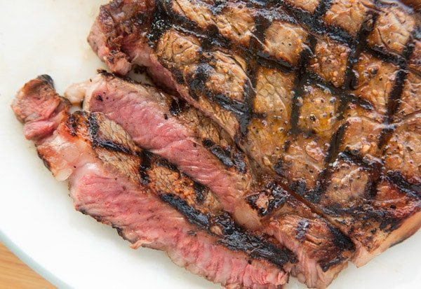 sliced medium rare ribeye with crosshatch marks on a white plate