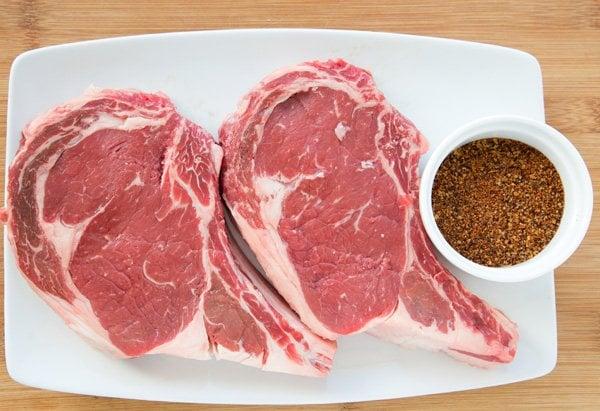 2 bone in ribeye steaks on a white platter with a ramekin of seasonings