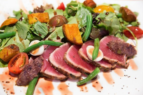 sliced rare tuna salad on a white plate