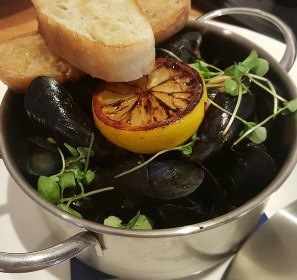 small pot of steamed mussels with grilled lemon half and toasted bread