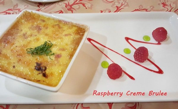 creme brulee with raspberries on a white plate