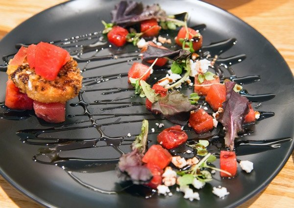 black plate with watermelon goat cheese salad