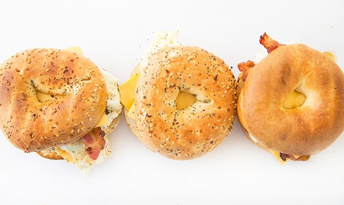 overhead view of two everything bagel sandwiches and one plain bagel sandwich