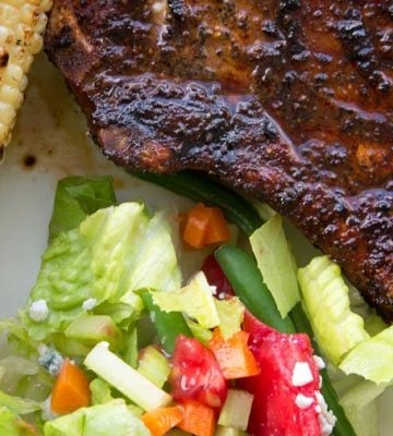 partial view of grilled pork chop with a salad