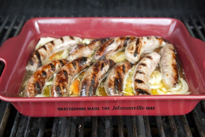 grill marked bratwurst in a baking dish with peppers onions and beer