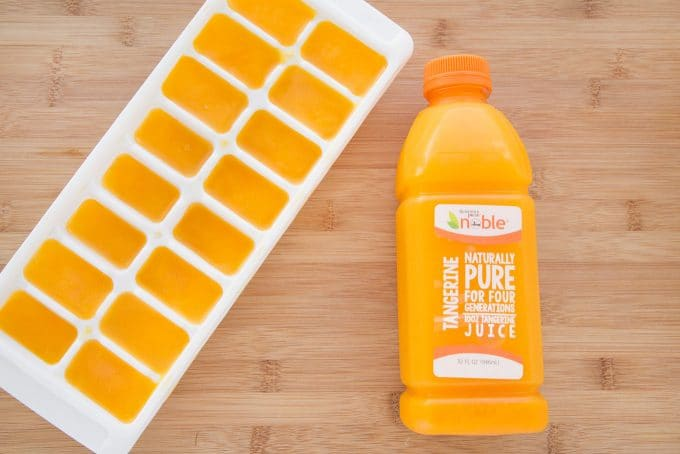 Tangerine Juice frozen in Ice Cube tray next to juice bottle