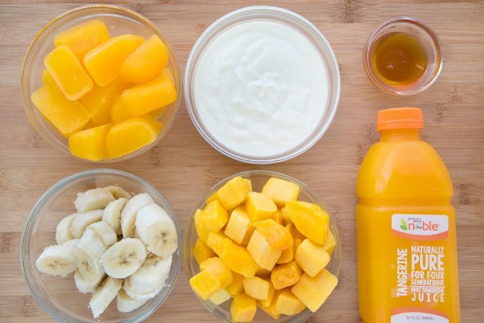 ingredients to make Tangerine Mango Smoothie on a wooden cutting board