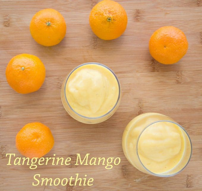overhead view of 2 glasses of Tangerine Mango Smoothie with tangerines along side on a wooden cutting board