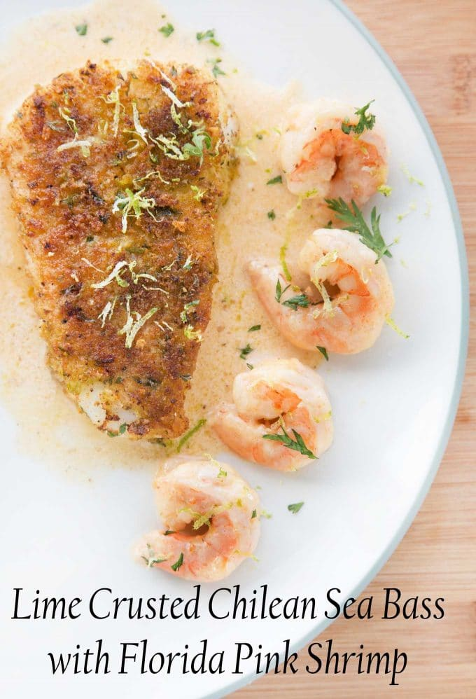 overhead view of Crusted Chilean Sea Bass with a row of shrimp  with a light sauce on a white plate