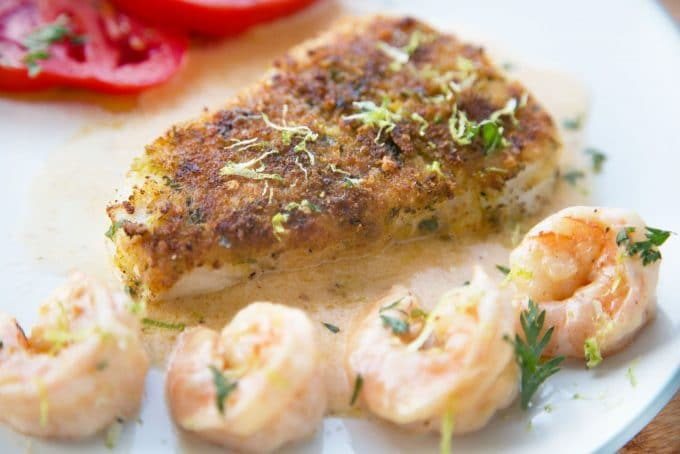 side  view of Crusted Chilean Sea Bass with a row of shrimp and the edge of tomato slices with a light sauce on a white plate