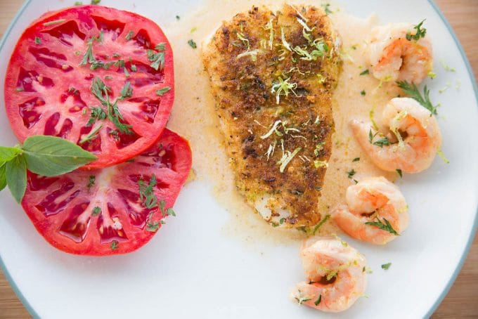 overhead view of Crusted Chilean Sea Bass with a row of shrimp and tomato slices with a light sauce on a white plate