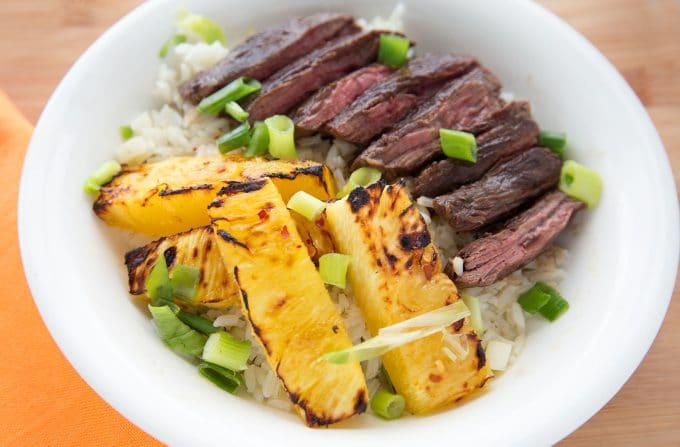 overhead shot of grilled pineapple and grilled flank steak over rice in a white bowl