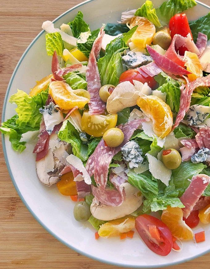 salad with meats, olives cheese, and fruit on a white plate on a cutting board