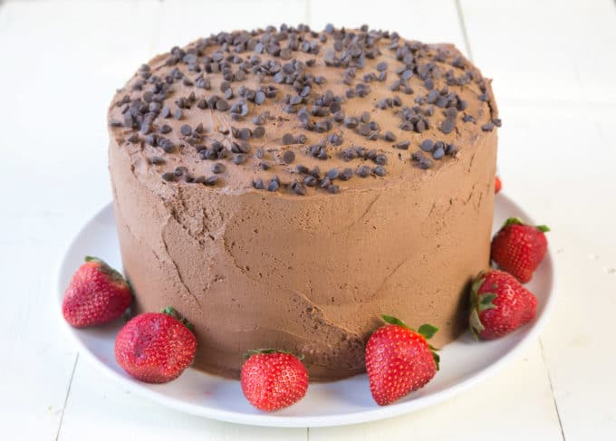 whole 4 layer chocolate cake with chocolate frosting and chocolate chips on the top, with whole strawberries around the cake sitting on a white plate with a strawberries around the plate