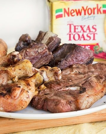 chicken legs, pork steak, sausage and beef short ribs on a white plate on top of a cutting board with a box of Texas Toast in the background