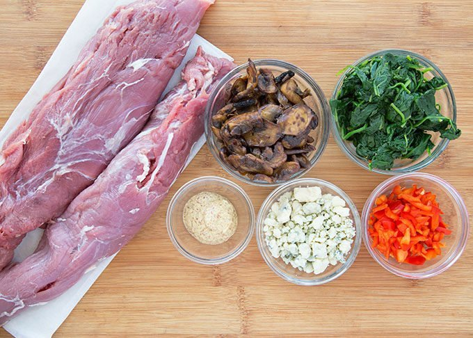 pork tenderloin and ingredients for stuffing in bowls sitting on a cutting board