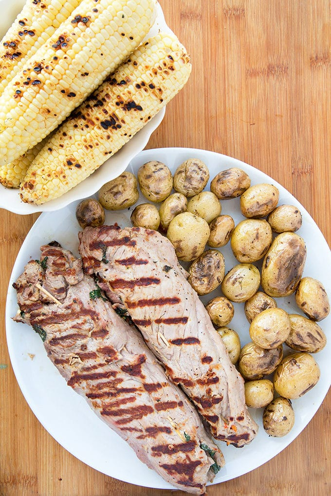 grilled stuffed pork tenderloin and baby potatoes on a white plate on a cutting board with a bowl of grilled corn on the cob