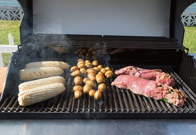corn, potatoes and stuffed pork tenderloin on the grill cooking