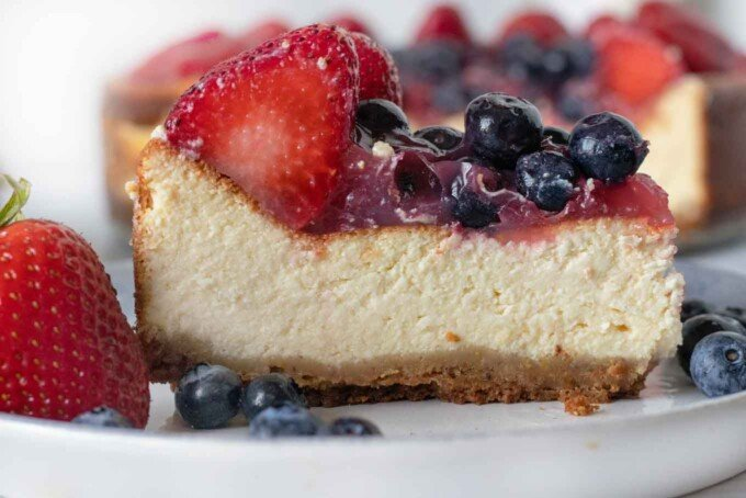 slice of cheesecake on a plate with berries