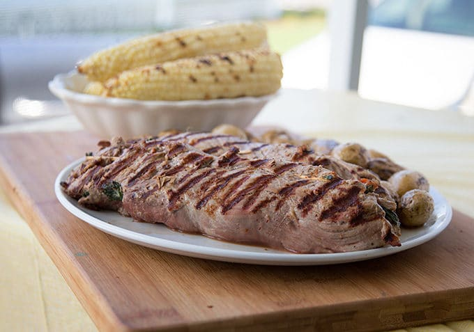 grilled stuffed pork tenderloin on a white plate on a cutting board with a bowl of grilled corn on the cob in the background