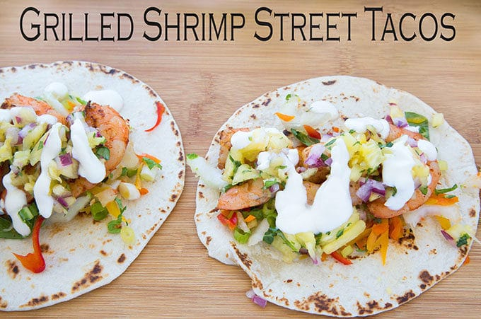 two grilled shrimp street tacos sitting on a cutting board