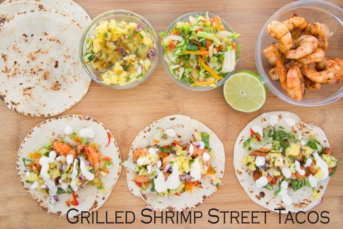 3 grilled street shrimp tacos with the ingredients to make more sitting on a cutting board