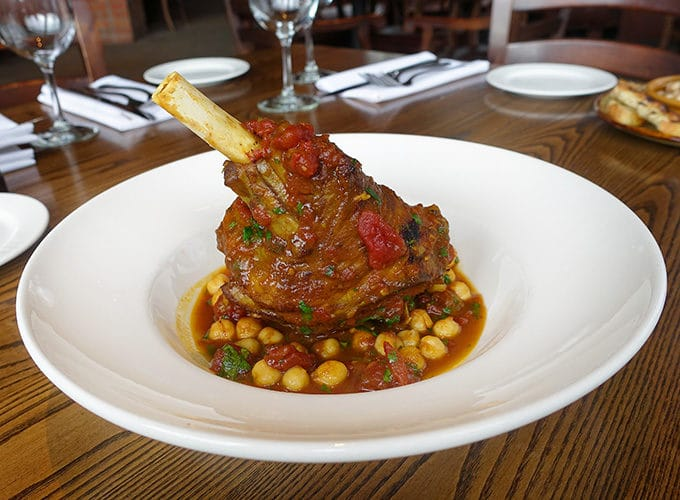 Braised Lamb Shank with tomato Chick Pea Ragout served in a white bowl on a table