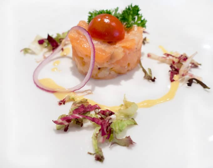 salmon tartare on a white plate with field greens and sauce
