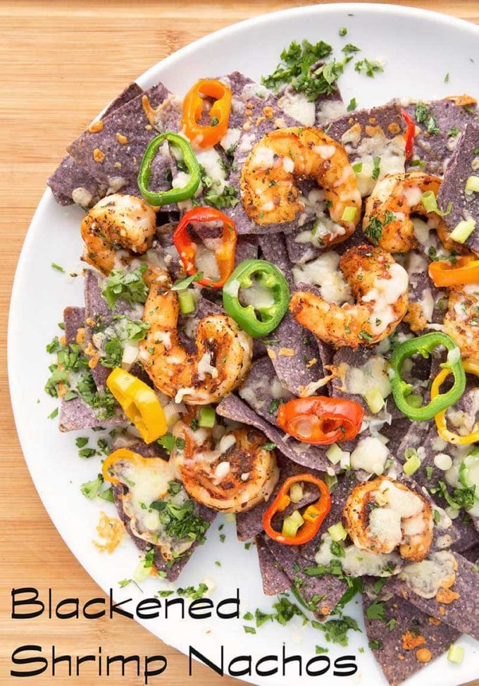 blackened shrimp nachos with melted cheese and peppers on a white plate sitting on a cutting board
