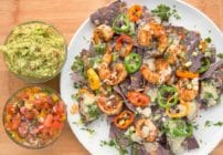 blackened shrimp nachos with melted cheese and peppers on a white plate with bowls of salsa and guacamole sitting on a cutting board