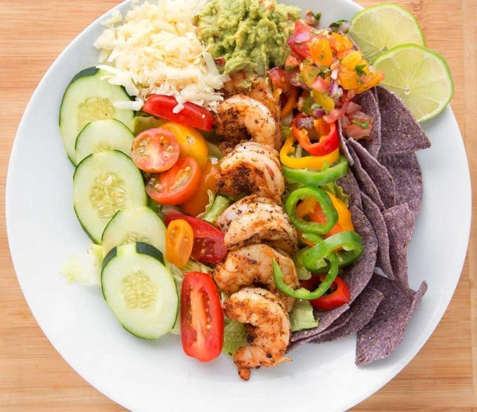 salad in a white bowl with blue tortilla chips, blackened shrimp, tomatoes, cucumbers, cheese, peppers, salsa and guacamole