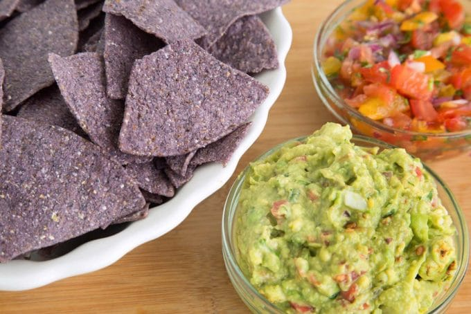 white bowl of blue tortilla chips with a bowl of guacamole and salsa