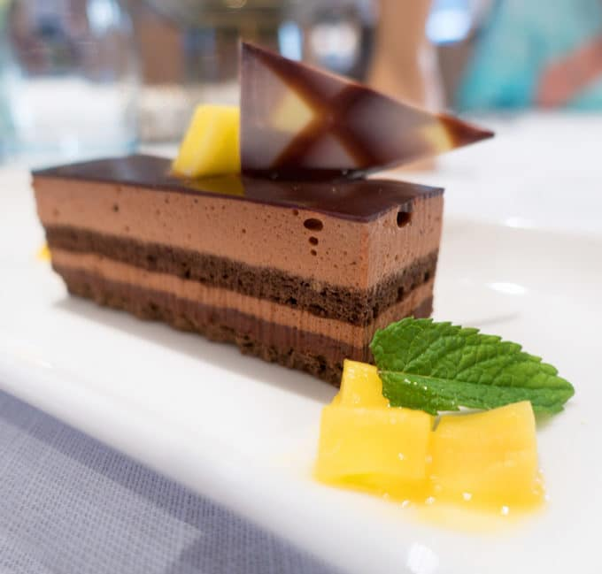 chocolate mousse cake on a white plate with mango chunks and a mint leaf
