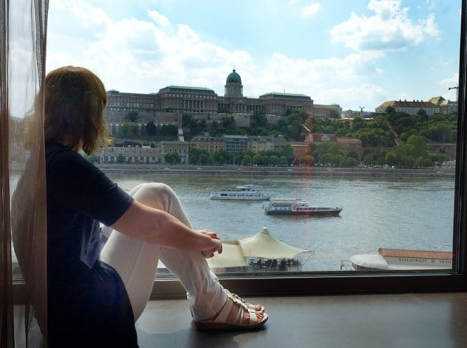 woman sitting on a window ledge looking out on the Danube river in Budapest