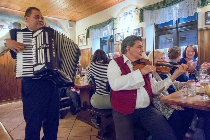 Musicians playing the accordion and violin in a Vienna woods wine bar