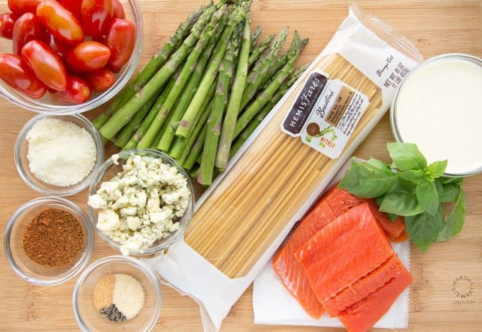 grape tomatoes in a small bowl, asparagus spears, package of bucatini pasta, 2 salmon fillets, small bowls of cheese, and spices, bowl of cream and sprig of parsley on a cutting board