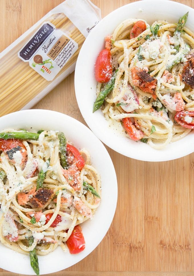 two white bowls filled with pasta mixed with salmon, asparagus, grape tomatoes and a cream sauce. sitting on a cutting board with a package of pasta