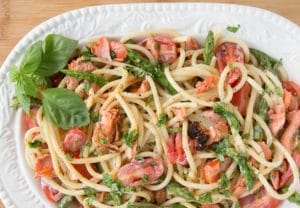oval serving bowl filled with pasta mixed with salmon, asparagus, grape tomatoes and a cream sauce. with a sprig of basil in the corner