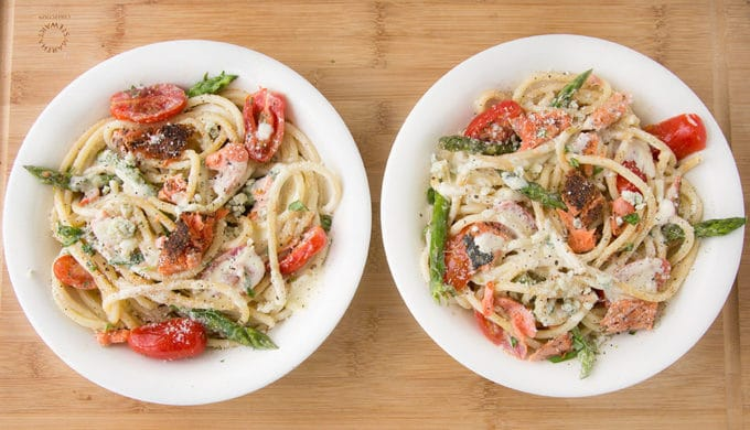 two white bowls filled with pasta mixed with salmon, asparagus, grape tomatoes and a cream sauce. sitting on a cutting board