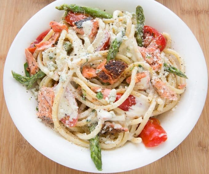 white bowl filled with pasta mixed with salmon, asparagus, grape tomatoes and a cream sauce. sitting on a cutting board