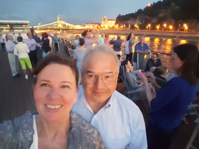 Chef Dennis and his wife on deck of a Viking River Cruise Boat at night in Budapest