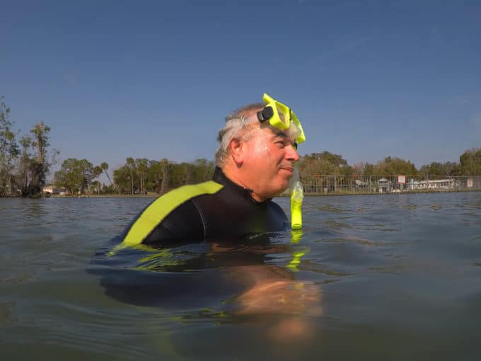 Chef Dennis in the water in a wet suit with snorkel gear
