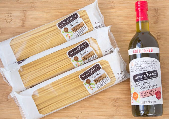 3 packages of bucatini pasta and a bottle of unfiltered olive oil sitting on a cutting board