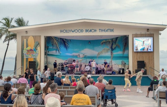 Hollywood beach theatre with aband performing as people seated watch and others dance