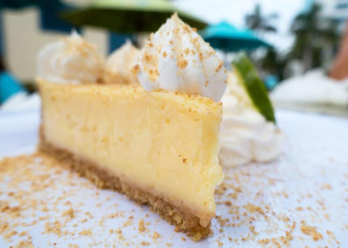 slice of key lime pie with whipped cream sitting on a white plate with graham cracker crumbs dusting the plate