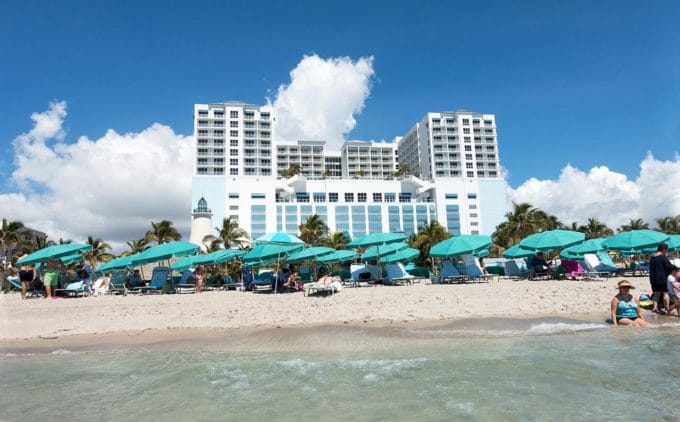 view of Margaritaville, Hollywood Beach Florida from the ocean. Water, sand , beach chairs and umbrellas in front of the resort